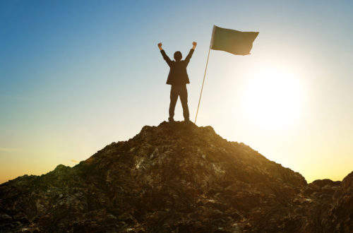 Photo of man with arms raised on summit of mountain